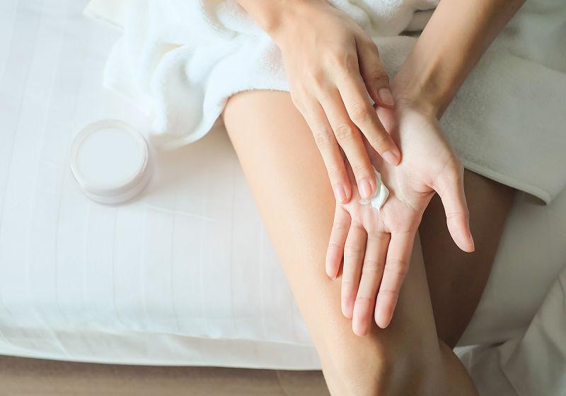 Mulher sentada com creme nas mãos para passar na perna