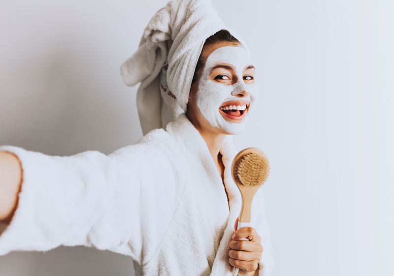 Mulher de roupão sorrindo com creme no rosto