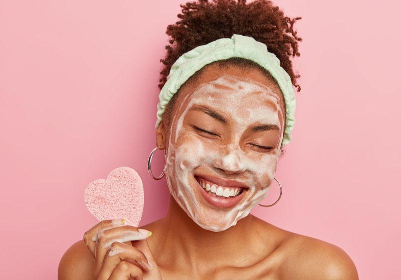 Mulher sorrindo passando sabonete no rosto