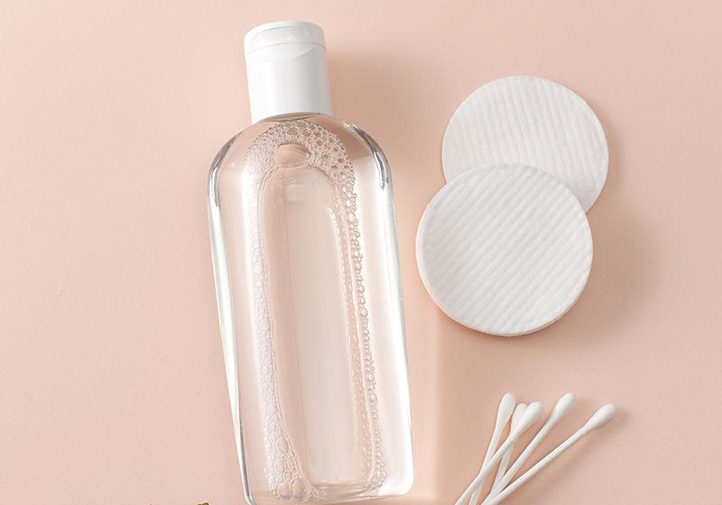 Frasco com água micelar, com rodelas de algodão e cotonetes para aplicação do lado