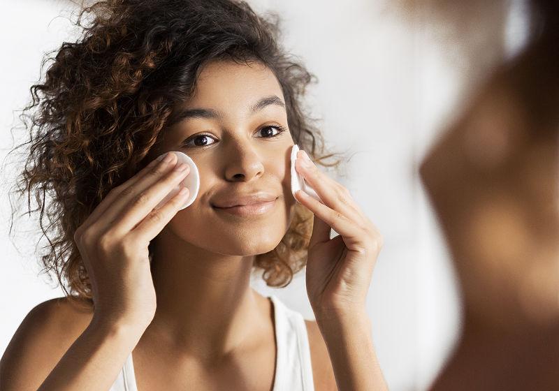 Moça aplicando água micela com dois algodões no rosto